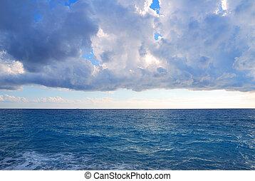Heavy clouds and vast deep blue sea waters
