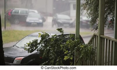 Heavy downpour on cars, trees and ground and a lightning...