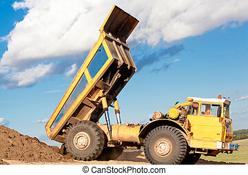 Heavy dump truck unloading soil on the sand at a ...