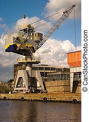 Heavy duty crane sitting on the edge of a harbor