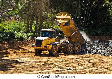 heavy duty dump truck dumping load of rock