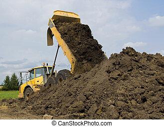 Heavy duty dump truck dumping soil