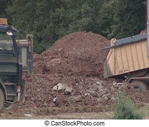 Heavy duty trucks. Truck dumps ground. Construction...