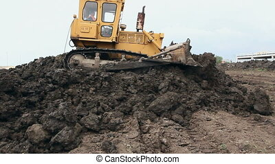 View on bulldozer, crawler while he is moving and leveling ground at building site.