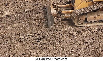 Heavy earthmover, bulldozer machine is leveling construction...