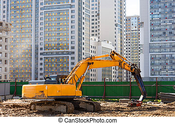 Heavy excavator in a working high frequency hydraulic vibratory mounted pile driver on road against the background of residential multi-storey buildings.