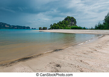 heavy gray clouds surging above the calm Andaman Sea in Thailand