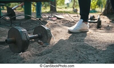 Heavy iron dumbbell falls on the sand in front of feet of athlete in white sneakers