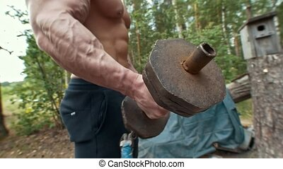 Heavy iron handmade dumbbell in hands of muscular man...