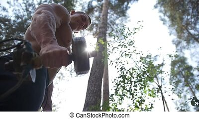 Heavy iron handmade dumbbell in hands of muscular man workouts in forest