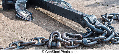 Heavy iron metal ship anchor with chain on gray asphalt.