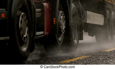 Heavy lorry driving over wet road - Heavy lorry driving over...