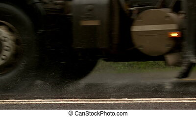Heavy lorry driving over wet road in slow motion