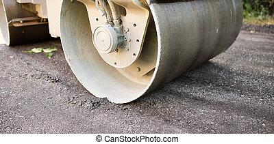 heavy machine rolls a new asphalt road