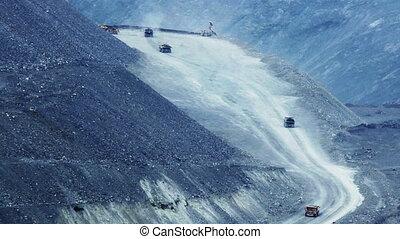 Heavy mining dump trucks moving along the opencast, far