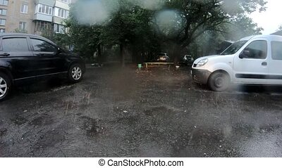 Heavy rain drops falling on asphalt road.