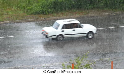 Heavy Rain Falling on the Asphalt Road. Old Car Rides by Road Through Raindrops