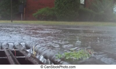 Heavy rain falling on the street and flowing through sewer drain
