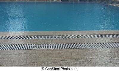 Heavy rain falls into a swimming pool. Not season, dirty...