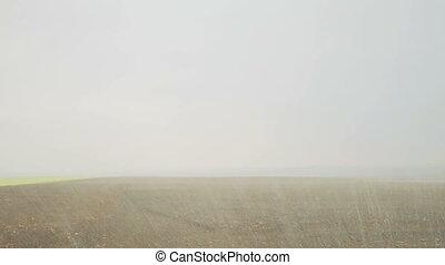 Heavy rain. Modern tractor cultivating field's soil