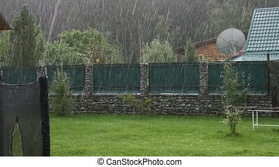 Heavy rain shower in backyard at unfinished house. slow...