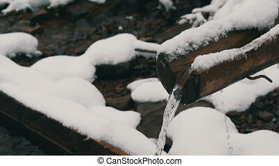 Heavy snow clean, transparent mountain water stream that flows down wooden gutter into special trough