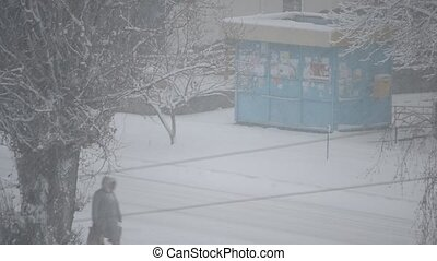 Heavy snow falling in city on background of kiosk and road