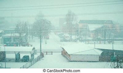 Heavy snow falling in winter on a road of small town