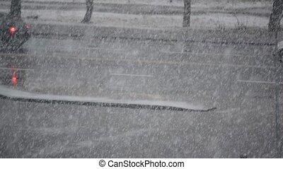 Heavy snow falls on background of road with cars driving