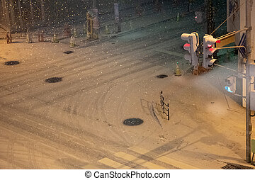 Heavy snow fell cover road at night during winter season at Chitose city, Japan