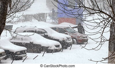 Heavy snowfall in the city. snow covered cars in the parking...