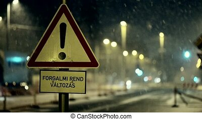 Heavy snowing at night with traffic sign closed off closeup