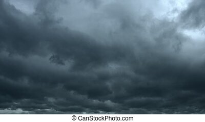 Heavy storm clouds in deep shades of gray, drifting slowly across the sky as lighting bolts streak downward. Video 4k