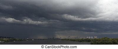Heavy, stormy clouds of contrasting color over the evening city
