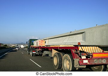 Heavy transportation truck lorry carrying a concrete big beam on a road in Europe