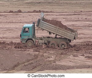 Heavy truck unload earth. Construction site equipment.