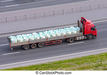Heavy truck with trailer and bulk cargo in bags- industrial sulfur, chemicals, poisons, dangerous goods rides on the highway in the city.