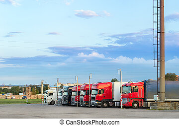 Heavy trucks with trailers loaded with merchandise, stand in...