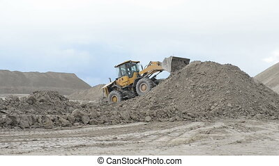 Heavy wheel loader working at open sand pit quarry