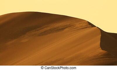 heavy wind blowing sand on top of desert dune