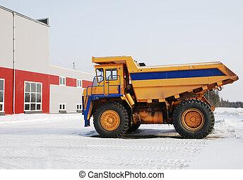 heavy yellow dump-truck near industrial building in winter