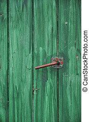 Hand painted green wooden door with metal handle