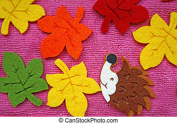 Hedgehog and colorful Maple leaves out of felt on a pink fabric