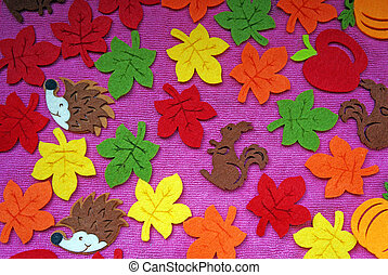 Hedgehog, squirrel and leaves out of felt on a pink fabric as a