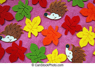 Hedgehogs and colorful Maple leaves out of felt on a pink fabric