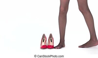 Heel shoes on white background. Legs in stockings. Emphasize...