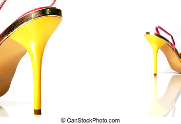 Yellow high heels separated by white space. Heel on the back is out of focus. Heels reflecting on white surface.
