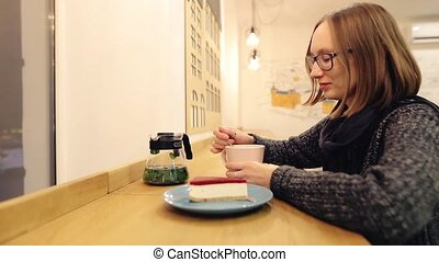 ?heerful girl enjoys a hot drink with dessert sitting in the evening in a cafe. Attractive caucasian woman in glasses with a good mood drinks mint tea with cinnamon, lime and honey.