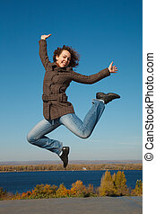 ?heerful girl in jump against dark blue sky. Productive leisure leads to success.