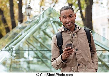 ?heerful, jovem, homem africano, segurando, seu, telefone,...